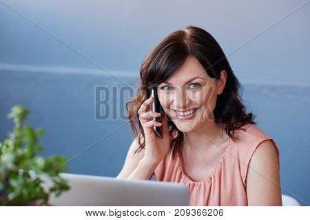 Portrait of a young businesswoman smiling while sitting alone at her desk in a modern office talking on a cellphone and working on a laptop