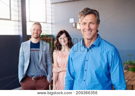 Portrait of a smiling mature businessman standing in a modern office with two work colleagues standing behind him in the background