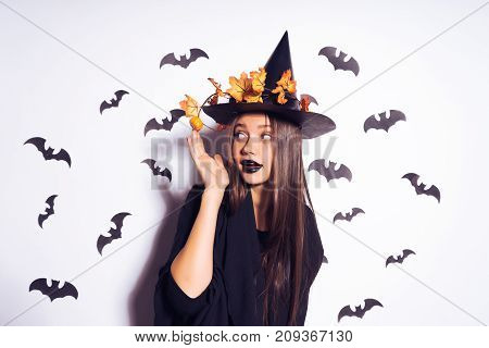 cute girl witch going to Halloween party and straightening her autumnal leaves on her black frightful hat. Against the background of a bunch of bats