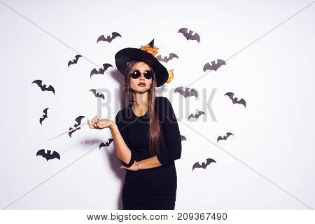 Wide Halloween party art design Halloween Witch in a black terrible hat smiles. Against the background of a bunch of bats.