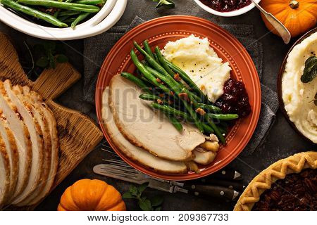 Thanksgiving plate with turkey, mashed potatoes, green beans and cranberry sauce
