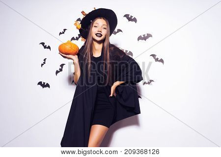 Wide Halloween party art design Halloween Witch with a carved Pumpkin and in a black terrible hat smiles. Against the background of a bunch of bats.