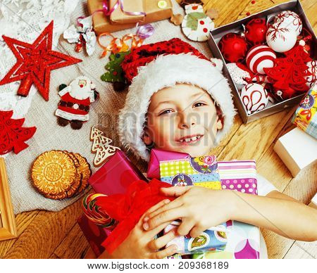 little cute boy with Christmas gifts at home. close up emotional happy smiling in mess with toys, lifestyle holiday real people concept