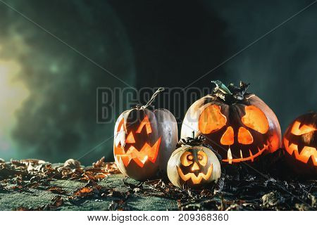 Halloween pumpkins at wood background. Carved scary faces of pumpkin. Night horror with full moon. October holiday. Pumpkin family