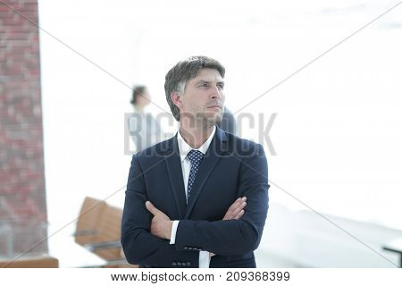 confident businessman stands and looks away.