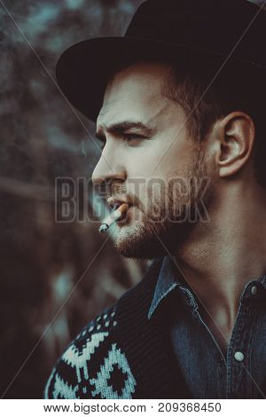 Close-up portrait of a handsome brutal man in cardigan and a hat smoking a cigarette outdoor over autumn nature background. Autumn fashion. Male fashion.