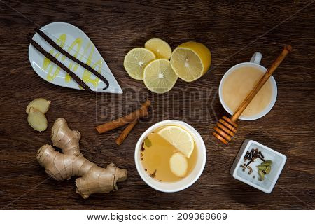 Winter hot drink and spices. Cup of tea , lemon, ginger, honey and cinnamon on wooden table. anti-cold products. Top view