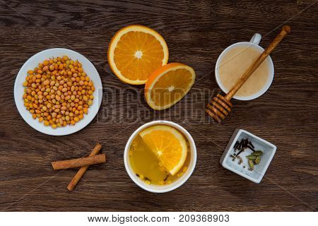 Winter warming tea and ingredients. Cup of tea, orange, sea buckthorn, honey and cinnamon on wooden table. anti-cold products. Top view