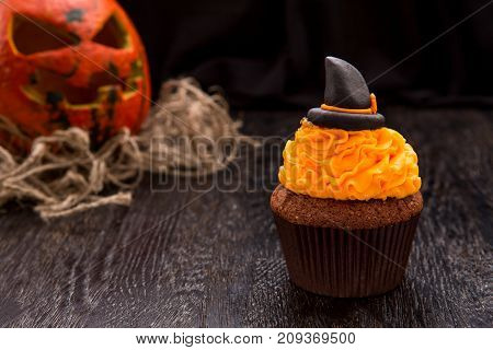 Halloween orange cupcake with witch's hat. Cupcake with monster pumpkin. Halloween cake on dark wooden table. Close up