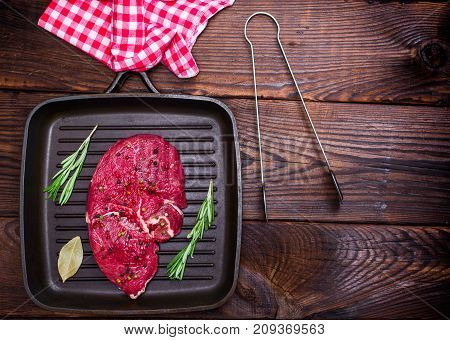 raw beef steak on a black quart pan empty space on the right