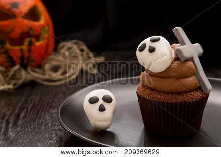 Halloween cupcake with tombstone cross and skulls. Cupcake with pumpkin. Halloween cake on dark wooden table. Close up