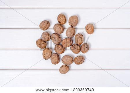 Walnuts whole on a white wooden background