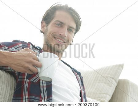 young man with laptop holding a cup sitting on the floor near the sofa