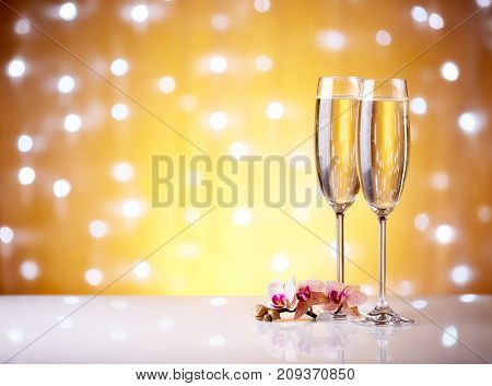 Two glasses with champange and flowers on a yellow background with lights of garland.