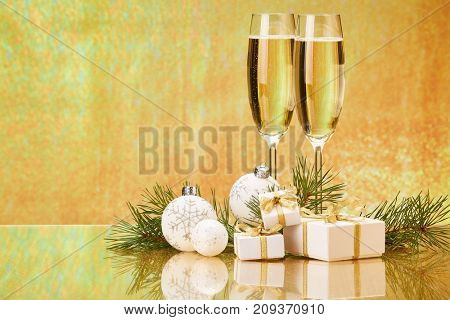 Two glasses with champange, fir tree branch, gift boxes and christmas decorations on a golden background.  New year and Christmas.