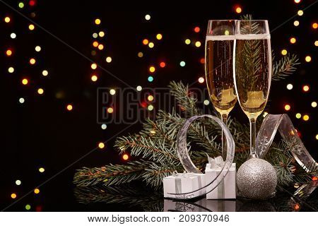 Two glasses with champange, fir tree branch with decoration, gift boxes on a black background with multi-colored lightes of garland.  New year and Christmas.