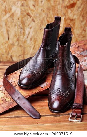 Brown Leather Chelsea Boots Polished With Leather Belt On Pine Board. Waxing Boots.copy Space