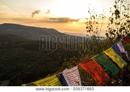 Colored Flags On Top Of A Mountain At Sunset