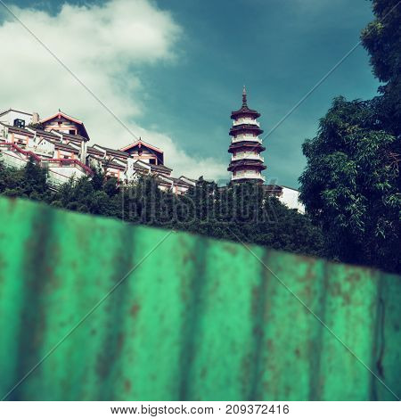 Hong Kong - October 2017: Pagoda with monastery surrounded by greenery viewed behind plastic fence.