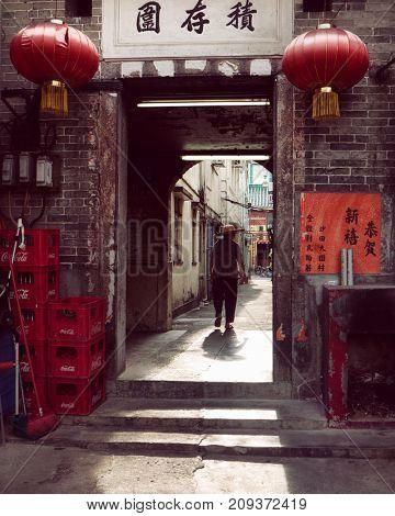 Hong Kong - October 2017: Woman in entrance gate of walled village. Tai Wai.
