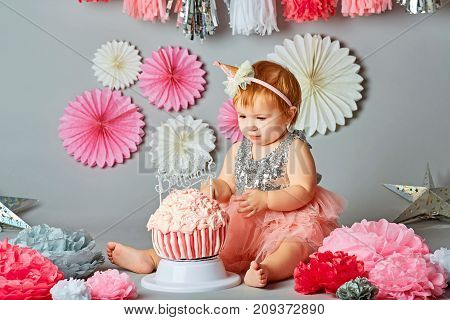 Baby girl and her birthday cake doing a smash cake in a studio