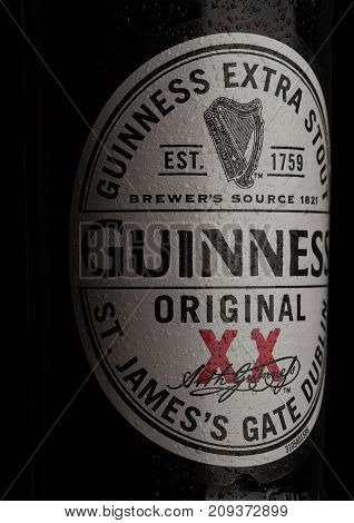 London, Uk - October 15, 2017: Guinness Extra Stout Beer Bottle Label On Black. Guinness Beer Has Be