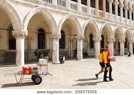 Venice, Italy - September 29, 2017: Two DHL postmen delivering parcels on the Piazza San Marco in Venice in front of Doge s Palace.