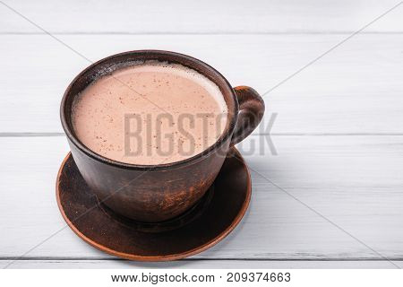 Hot cocoa with milk in brown clay cup on table of white wooden planks.