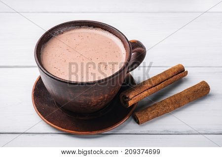 Hot cocoa with milk in brown clay cup and cinnamon sticks on table of white wooden planks.