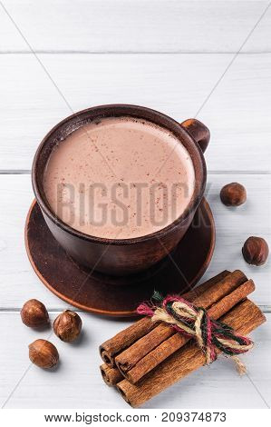 Hot cocoa with milk in brown clay cup hazelnut and cinnamon sticks on table of white wooden planks.