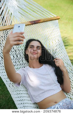 Relaxed Young Woman Looking At Mobile Phone In Hammock