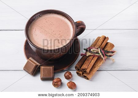 Hot cocoa with milk in brown clay cup broken chocolate cubes hazelnut and cinnamon sticks on white wooden planks.
