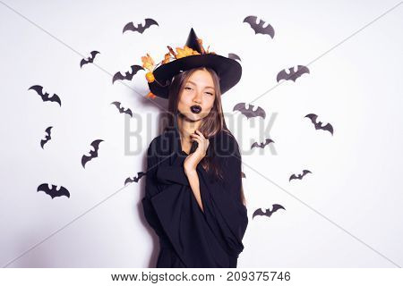 a young  gothic girl in a black witch hat, celebrates halloween. against the background of drawings of bats