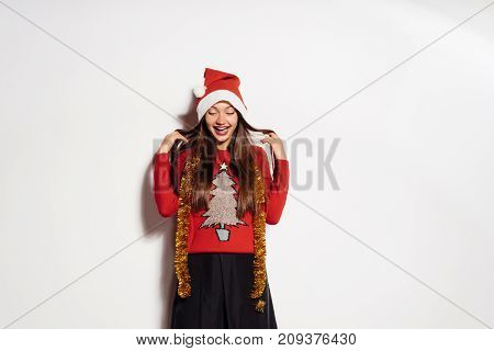 young happy girl celebrates New Year and Christmas, in a red cap, festive sweater and gold tinsel