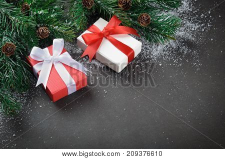 Two christmas gift boxes with bows on a dark stone background fir brances with cones and snowflakes copy space