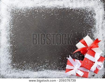 Three christmas gift boxes with bows in the corner of a dark background frame made of snowflakes top view copy space
