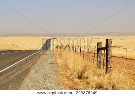 a black-top road leading into the hazy distance with a barb-wire fence running along the side of the road. Weeds grow by the road and a golden field is in the background. Old, wooden fence posts are in the foreground.