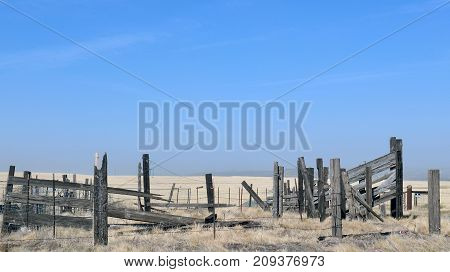 An isolated old, dilapidated, wooden corral sitting in an empty field with lots of blue sky above. It is held together by wire fencing and barbed wire.