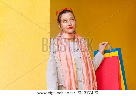 Portrait Of  Pretty Pondering Girl With New Clothes In Packets. Looking Away And Thinking