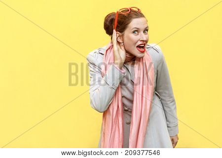 I Can Not Hear You. Beautiful Red Head Girl . Studio Shot, Yellow Background