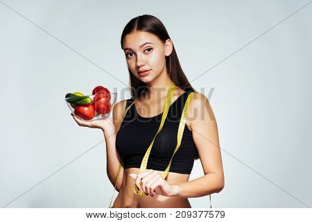 lovely beautiful girl is going to make a light salad of tomatoes and cucumbers, proper nutrition, diet, beautiful body