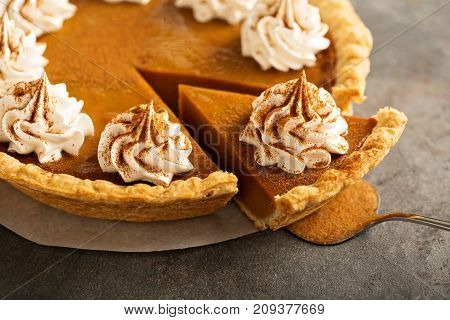 Sweet pumpkin pie decorated with whipped cream with a slice taken