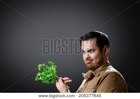 The man with neglect looks at parsley. Isolated on dark grey background, studio shot. Diet concept.