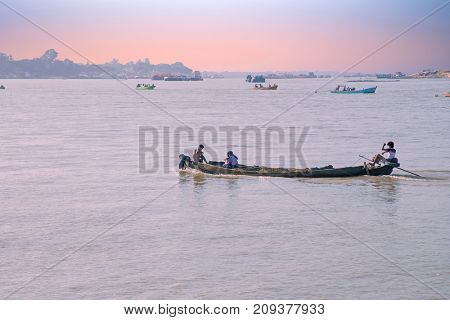 Boats on the Irrawaddy River at sunrise. The Irrawady river is a river that flows from north to south through Myanmar and is the most important waterway