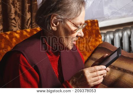 senior women with glasses reading ebook sitting in her sofa