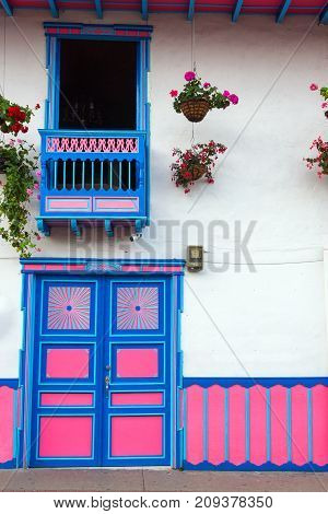 Brightly colored door and balcony of a colonial building in Salento Colombia