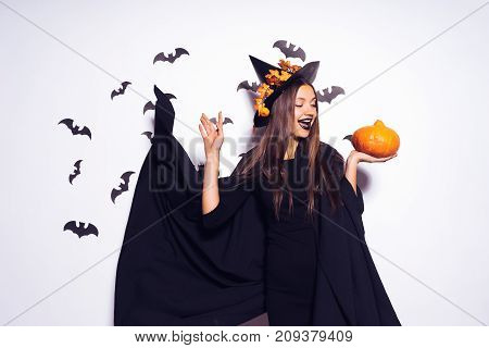 young laughing girl with black lipstick in the form of a witch for halloween, her black cloak fluttering, holding a pumpkin in her hands