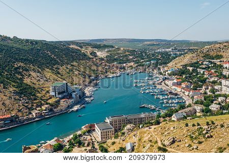 Beautiful aerial view of the Black Sea coast and the city Balaklava in clear sunny summer day. Balaklava Bay, Crimea