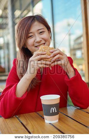 KALININGRAD, RUSSIA - CIRCA OCTOBER, 2017: pretty woman eat at McDonald's restaurant.