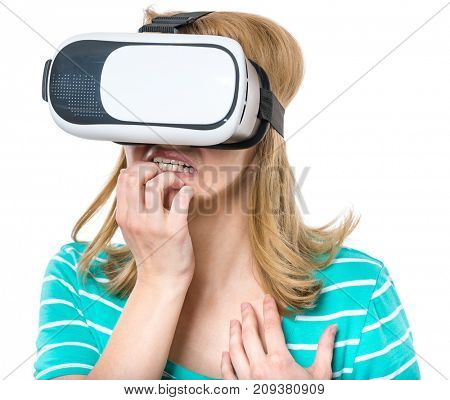 Amazed young woman wearing virtual reality goggles watching movies or playing video games, isolated on white background. Surprised girl worried and scared making face looking in VR glasses.